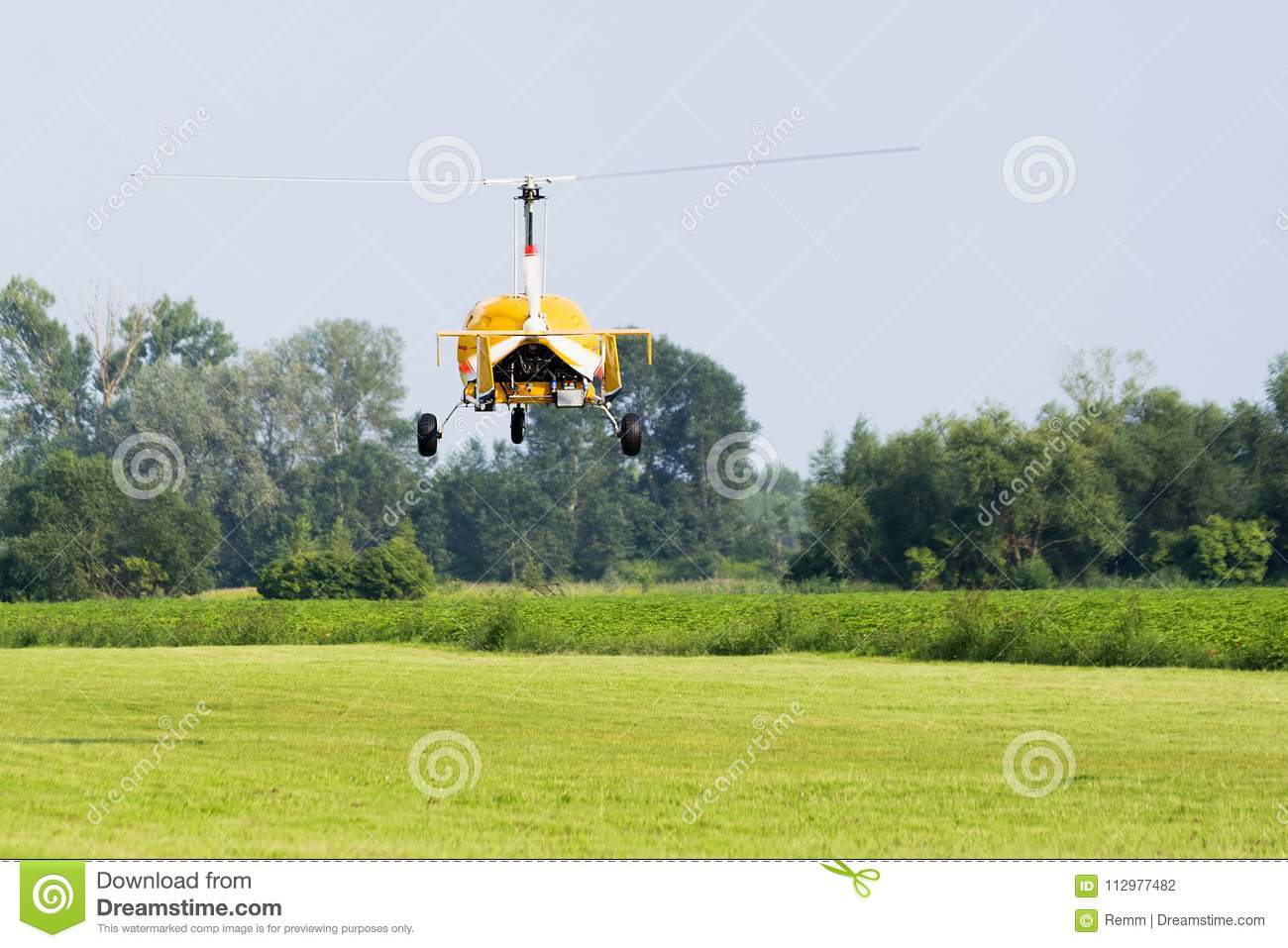Yellow gyroplane departing from the airport