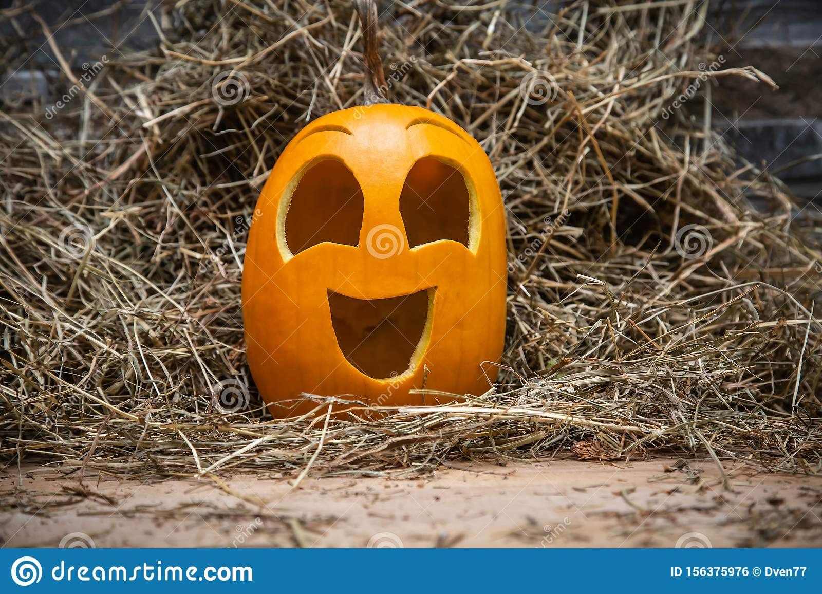 Yellow and happy smiling pumpkin. Halloween symbol on a gray stone wall background, stands on a hay and a wooden stand. Jack o