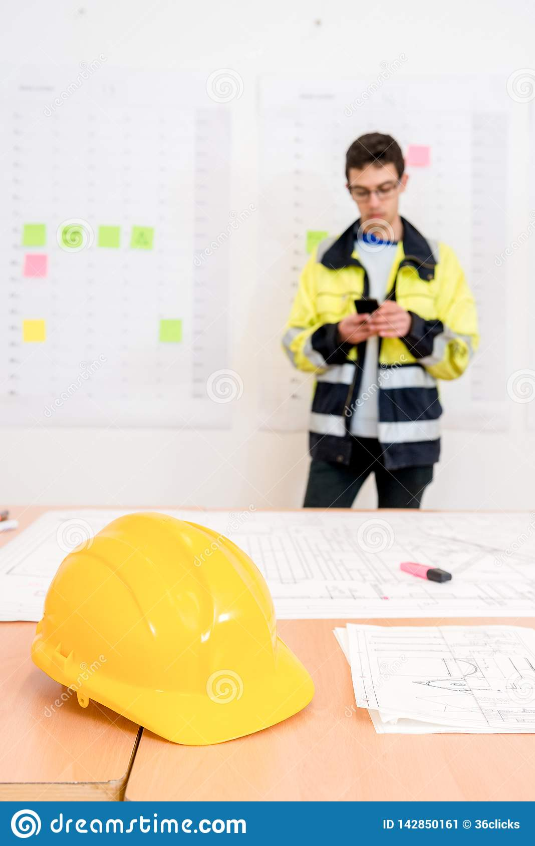 Yellow Helmet On Table With Contractor Using Phone In Office