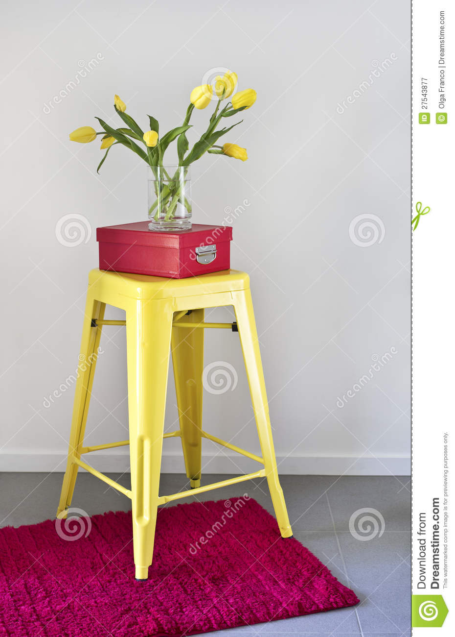 Yellow industrial stool and red rug