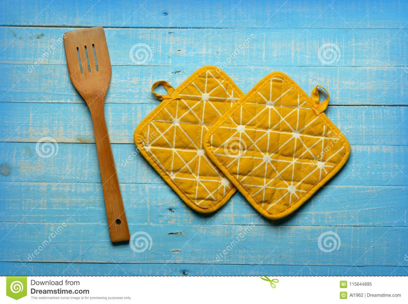 Yellow Kitchen Pot Holders On Blue Table Stock Image - Image of ...