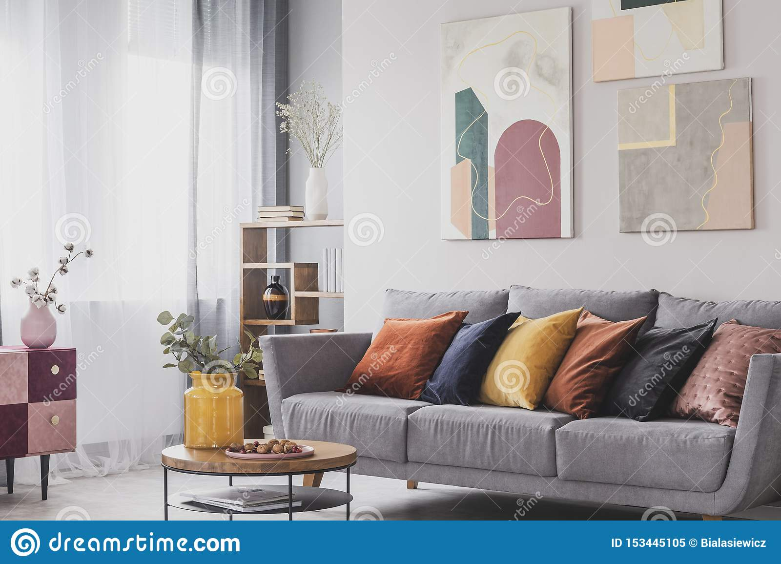 Yellow Orange Black And Brown Pillows On Comfortable Grey