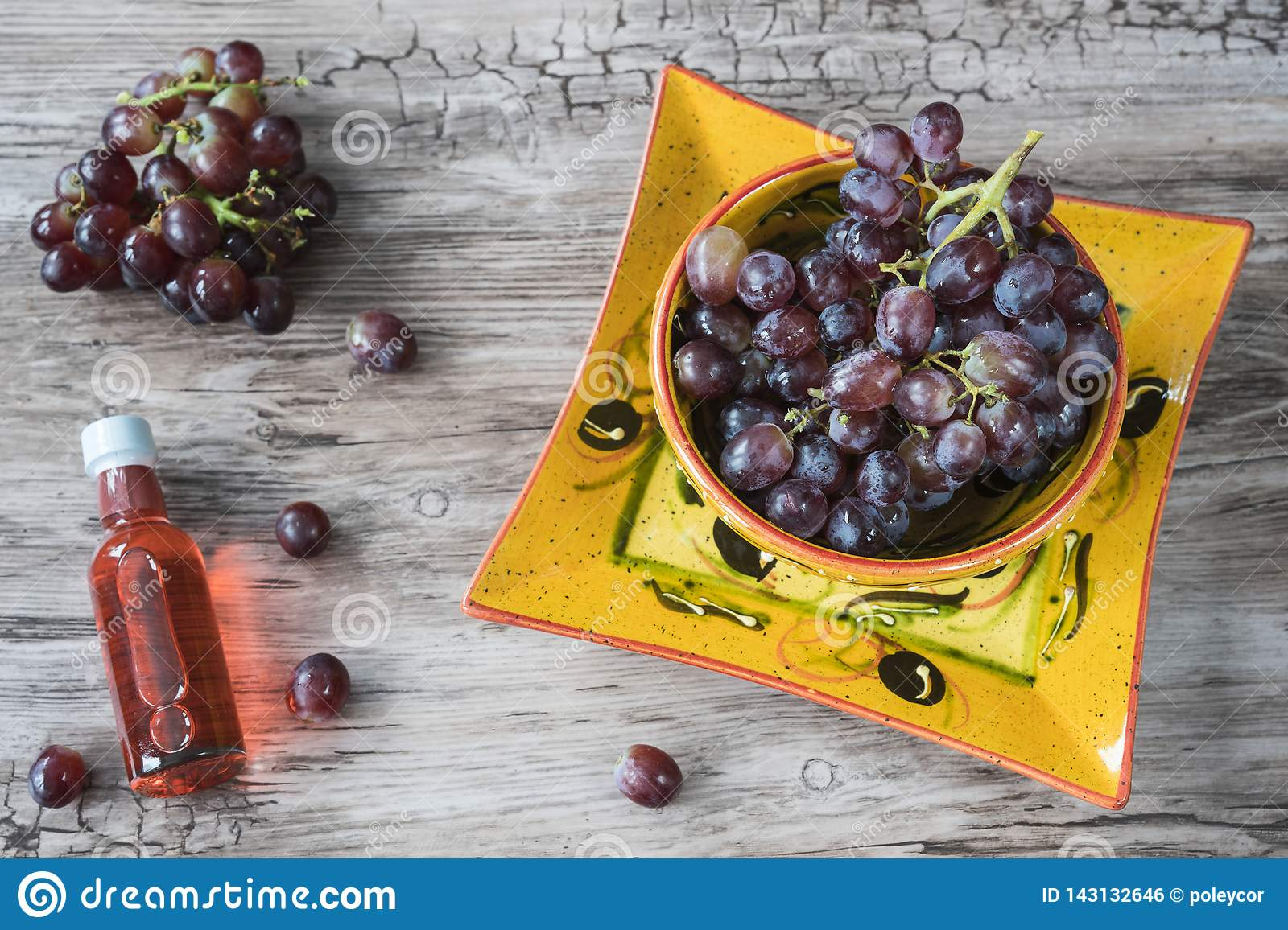 Bunch of red grapes in orange bowl, against wooden background