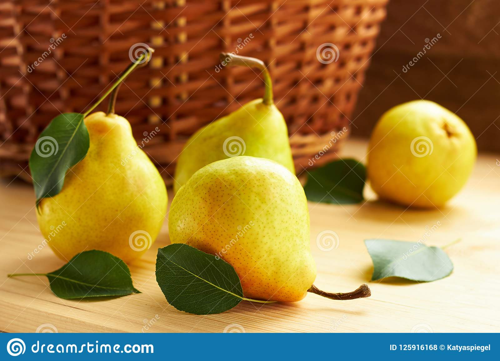 Fresh pears with green leaves in front of wattled basket on wooden background