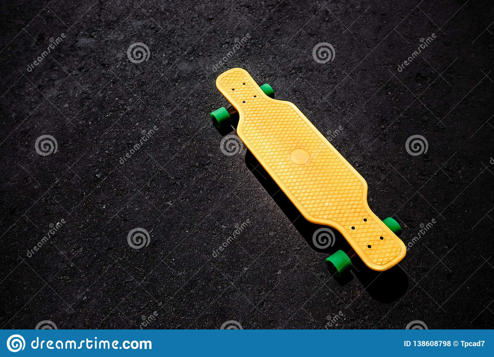 Yellow plastic longboard on the asphalt surface