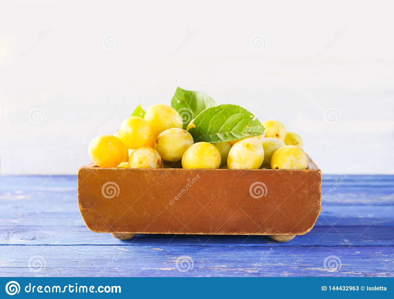 Yellow plums. Ripe fruits in a wooden box on white background