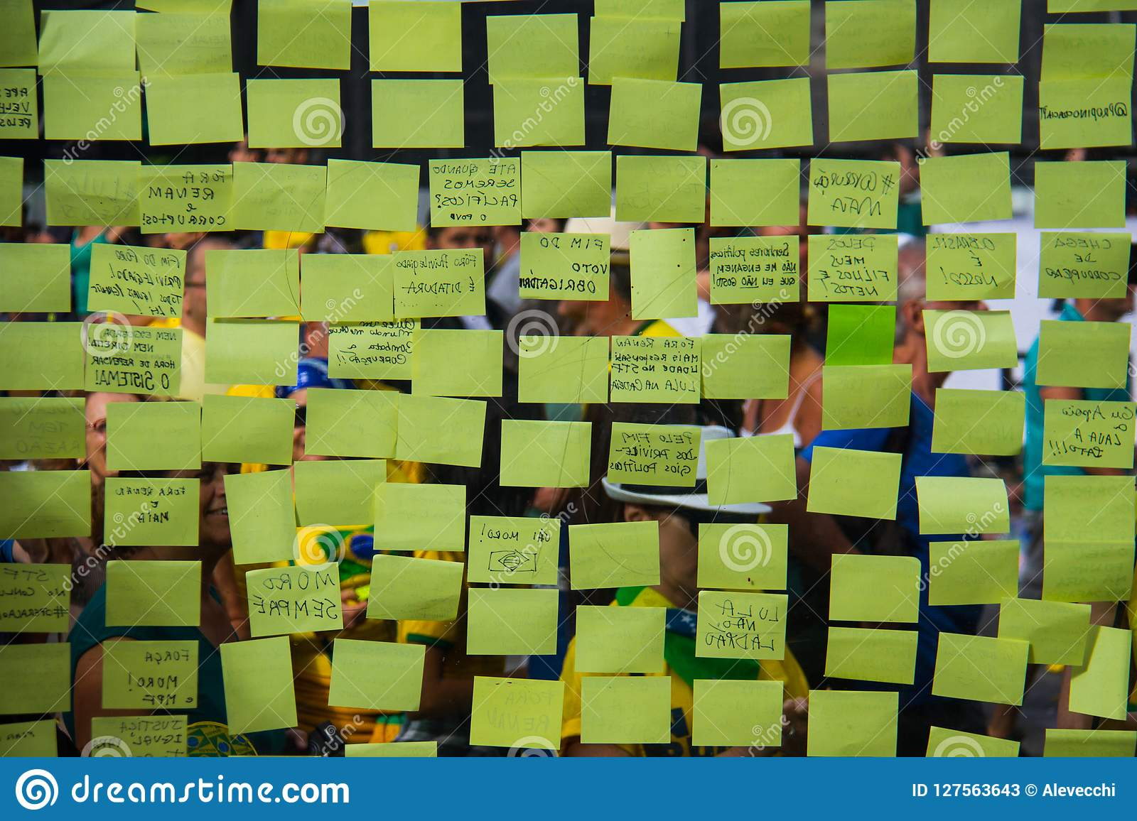 Yellow post-it sticky notes on a glass wall.
