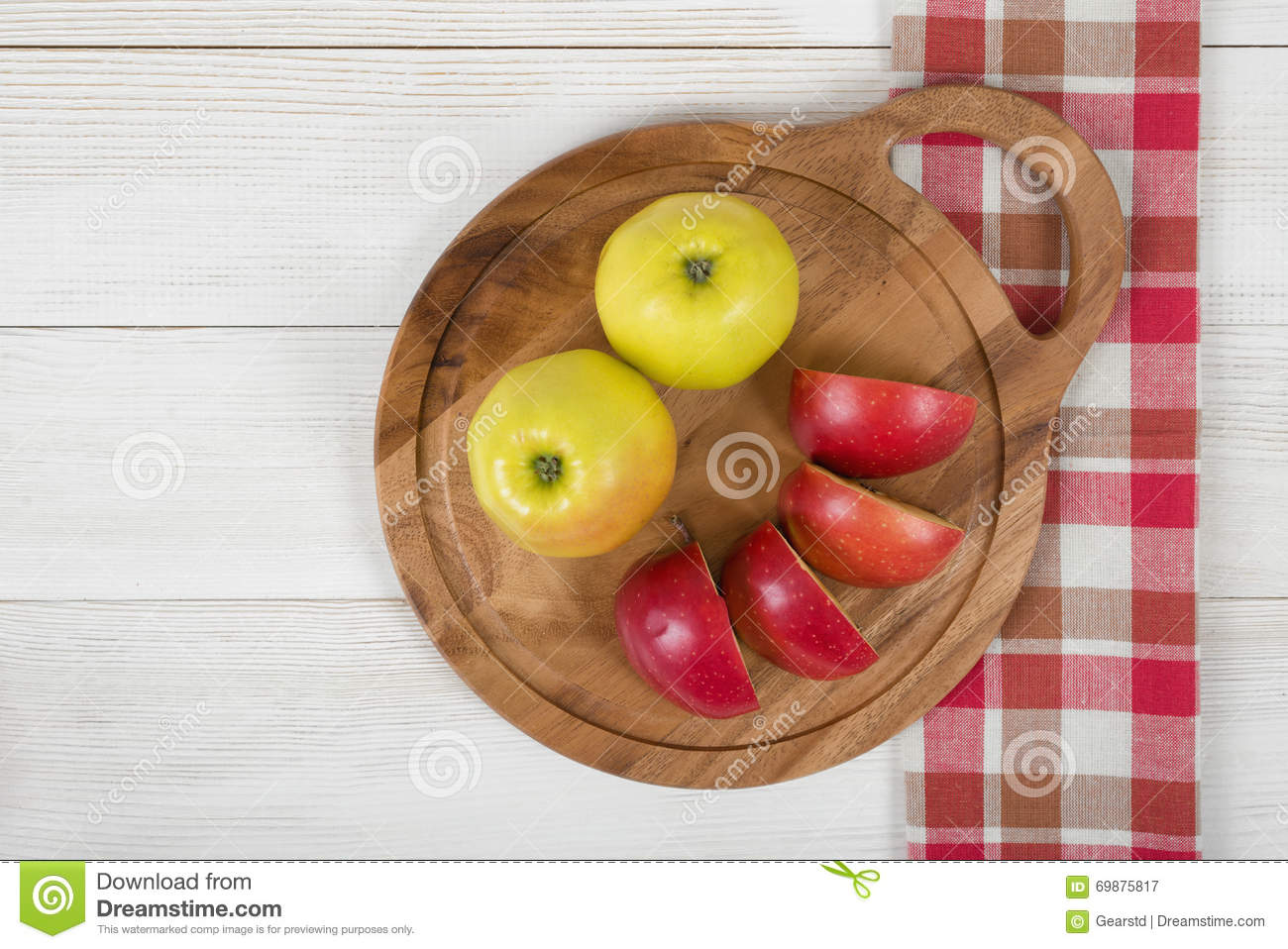 Yellow and red apples laid on a cutting wooden board