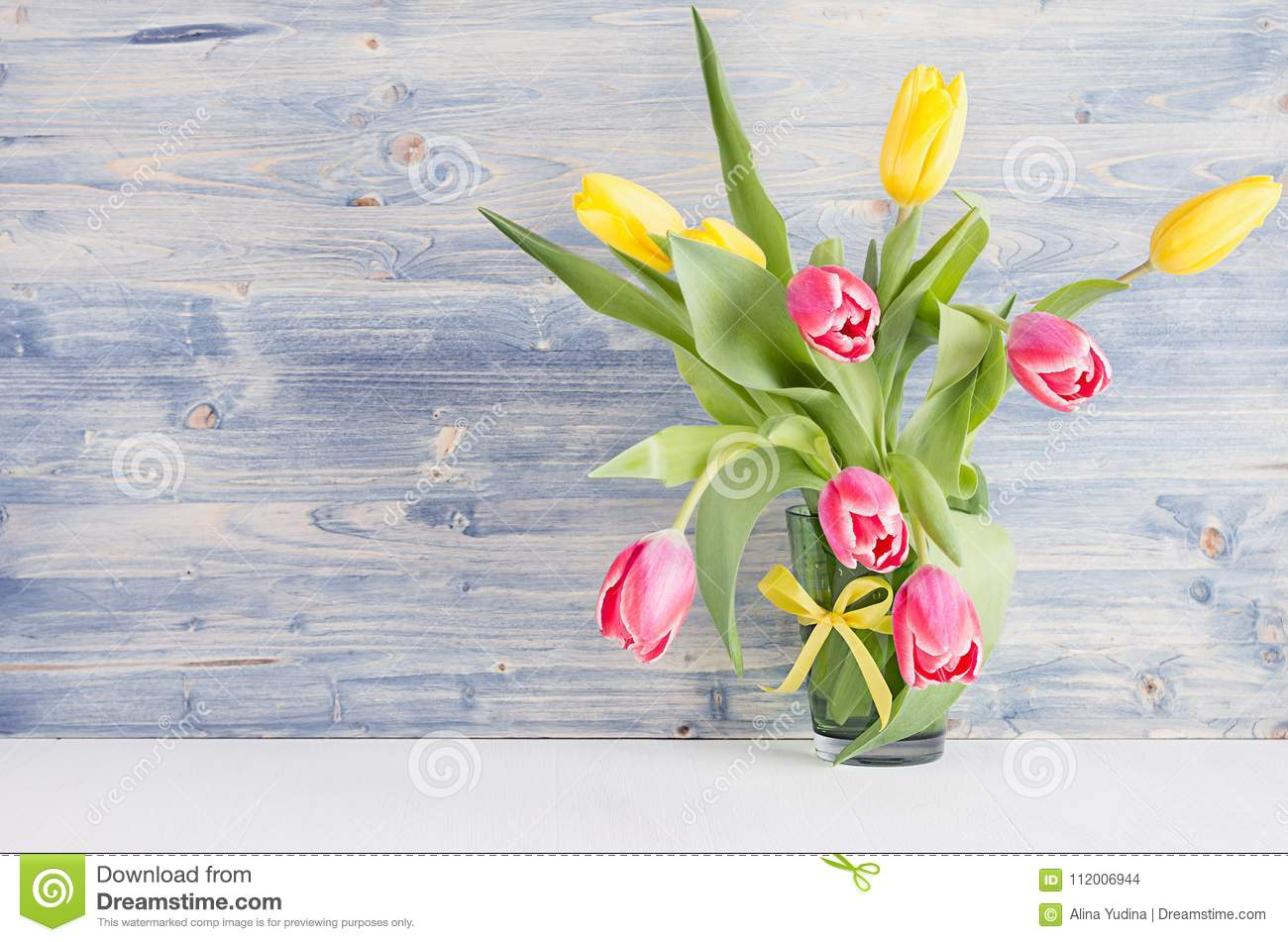 Yellow and red tulips in vase on blue shabby chic wood board. April spring background, home interior, decor.