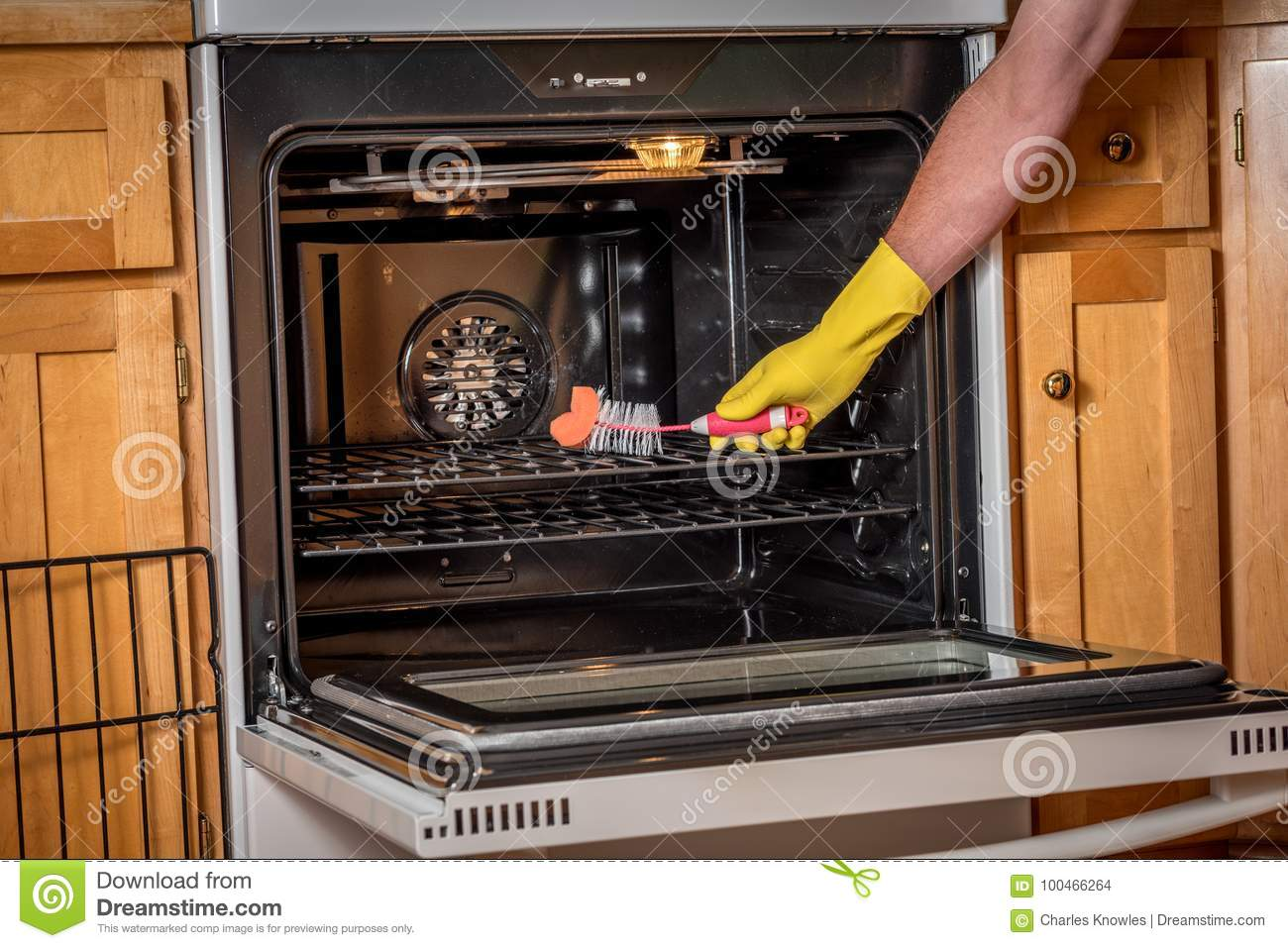 Convection Oven Cleaning Demonstration With A Hand Brush Stock Photo