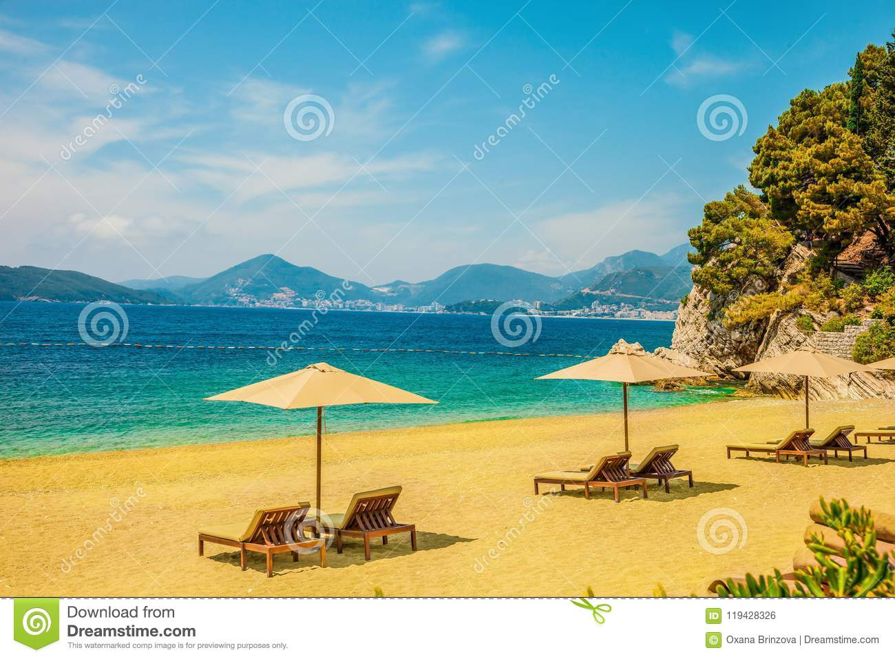 Yellow sandy beach with sun loungers on a Sunny day. Mountain peaks visible in the distance. Beautiful sea background.