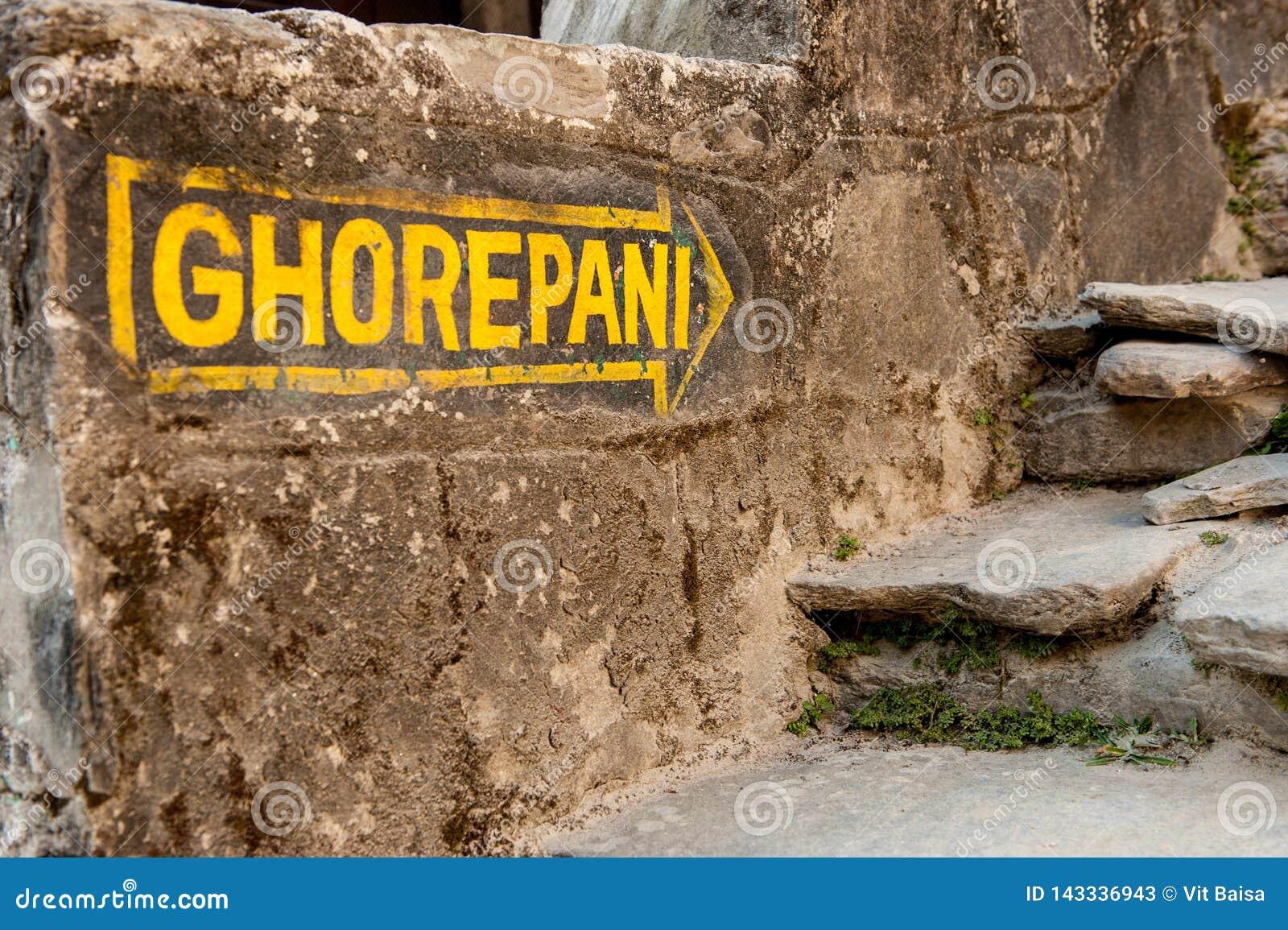 Yellow signpost arrow on the stone wall heading to Ghorepani on Poon Hill, Annapurna circuit trek, Nepal, Himalayas