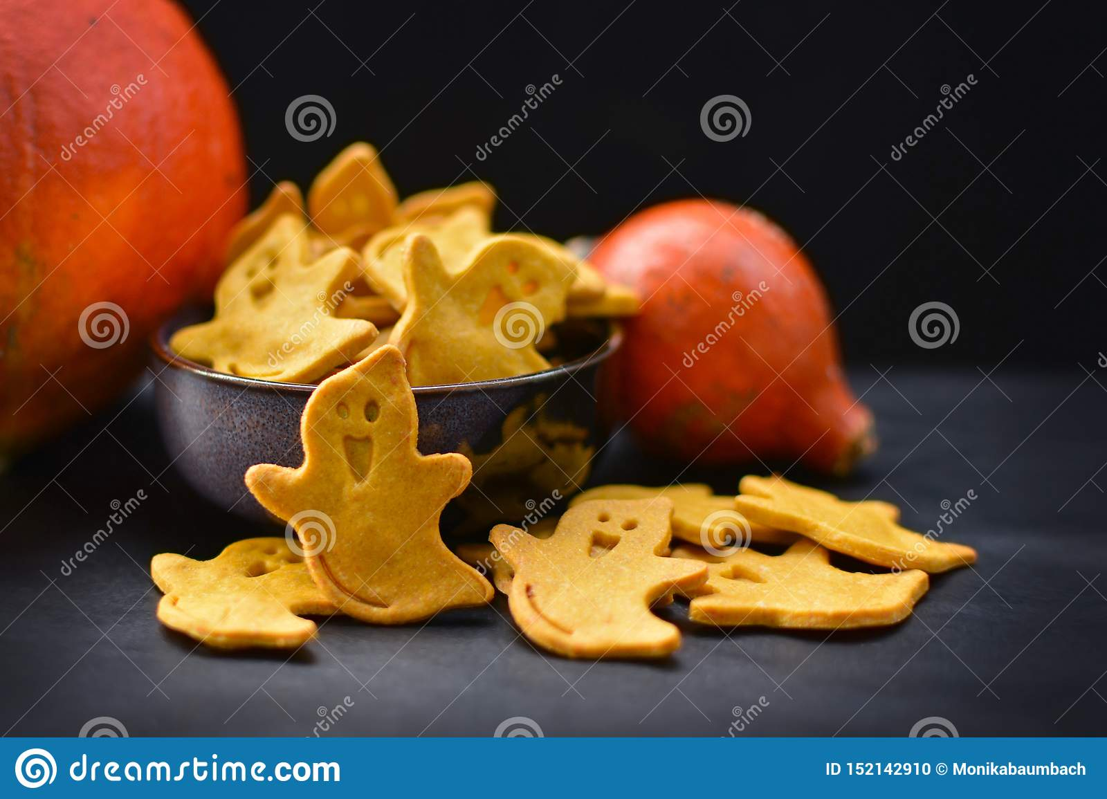 Yellow spooky ghost shaped Halloween cookies with orange pumpkins on dark background