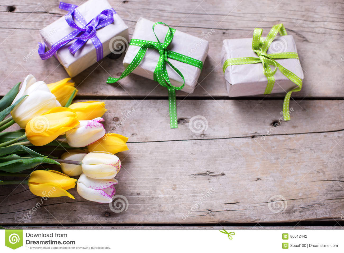 Yellow spring tulips and box with presents on wooden backgroun