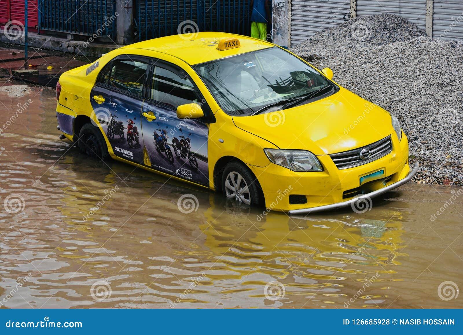 Yellow taxi cab stuck in the rain water in Bangladesh