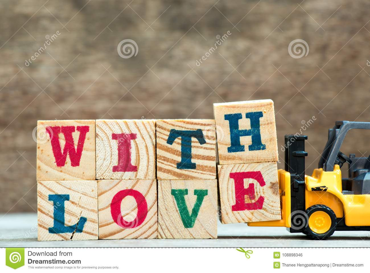 Yellow Toy Forklift Hold Letter Block H And E To Word With Love