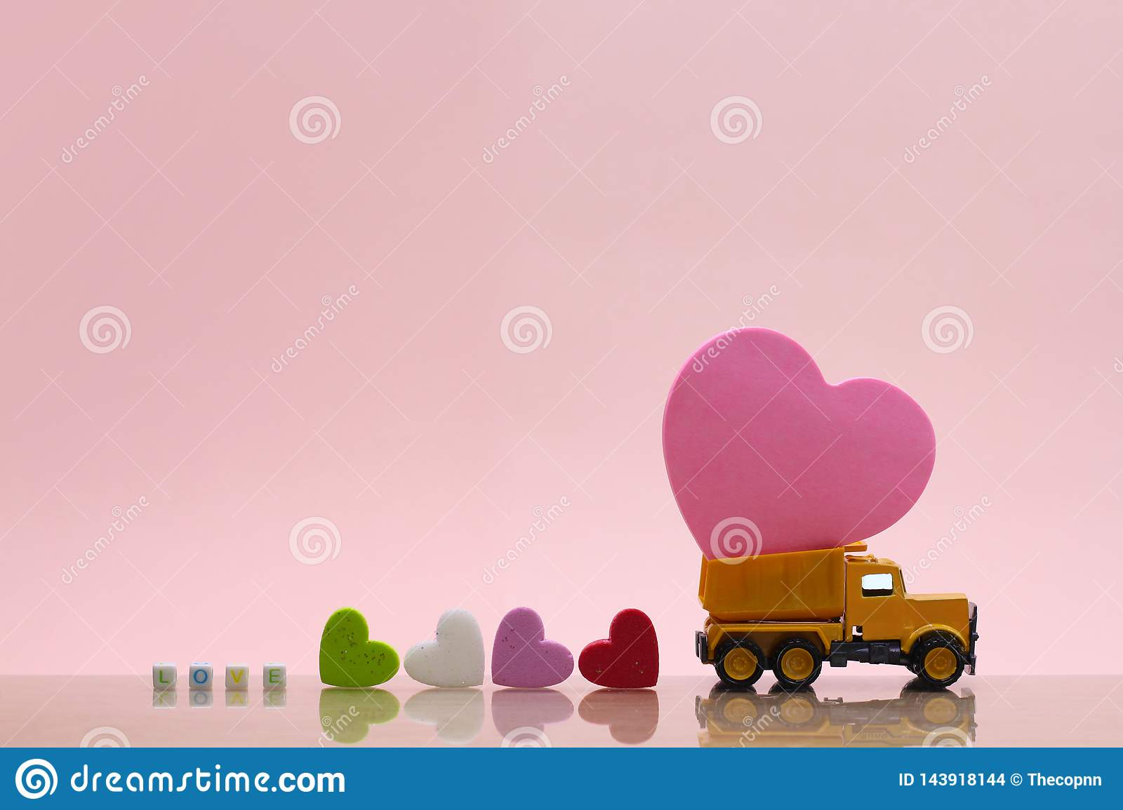 Yellow toy truck carry on pink heart on pink background