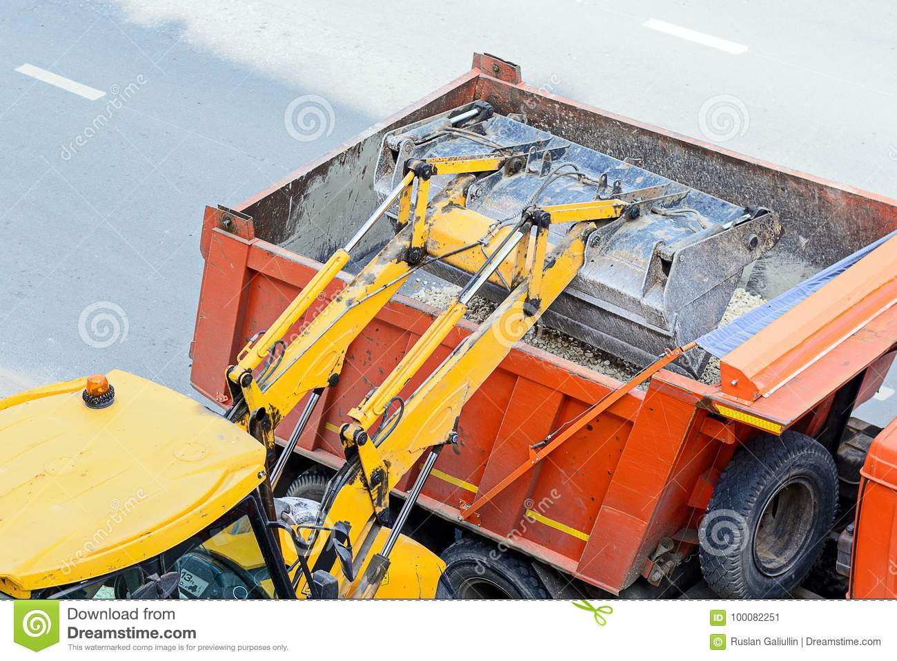 Tractor loading gravel into a truck. road works