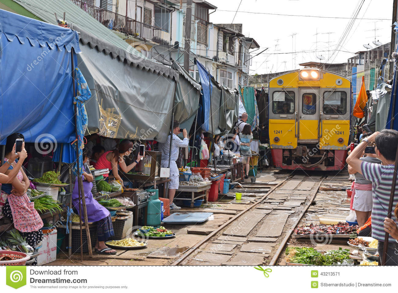 The yellow train has arrived while people are taking pictures and videos at Maeklong Railway Market.
