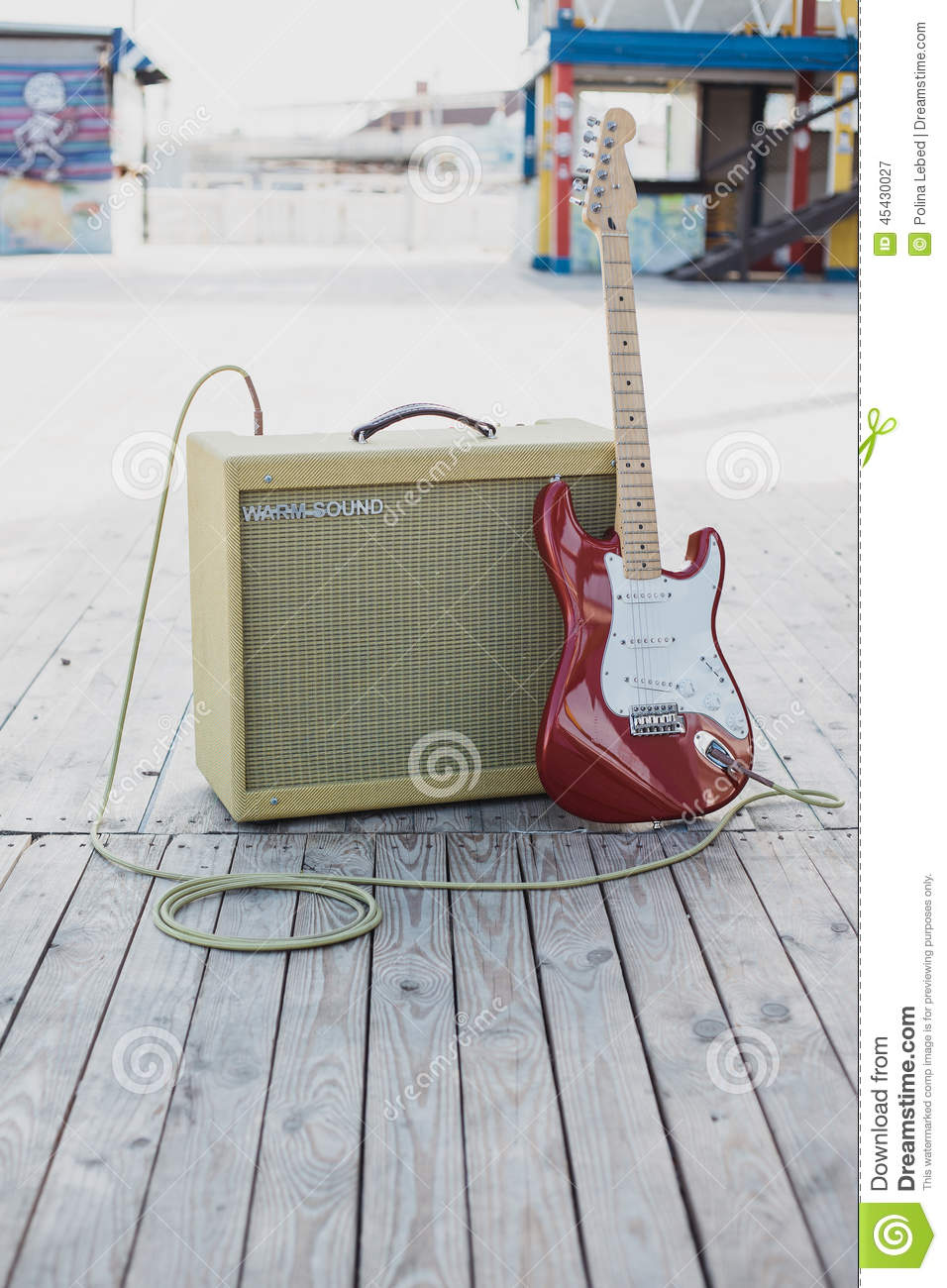 Yellow vintage guitar aplifier with cable and red electric guitar