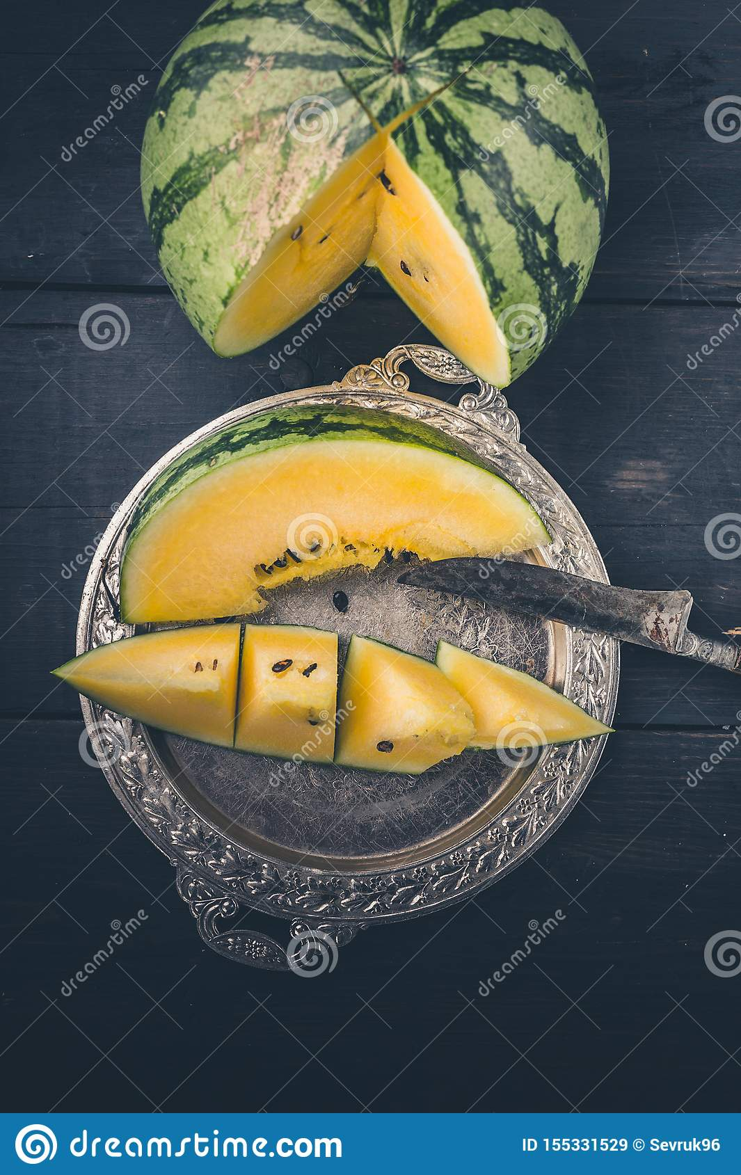 Yellow watermelon, slice of watermelon on a silver plate and knife on a dark wooden background. Vertical shot