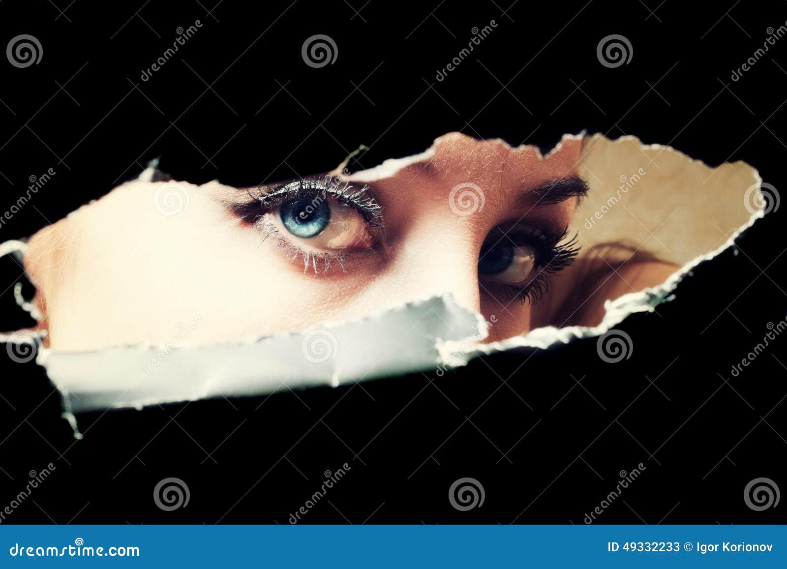 Yeux bleus de jeune femme piaulant par un trou