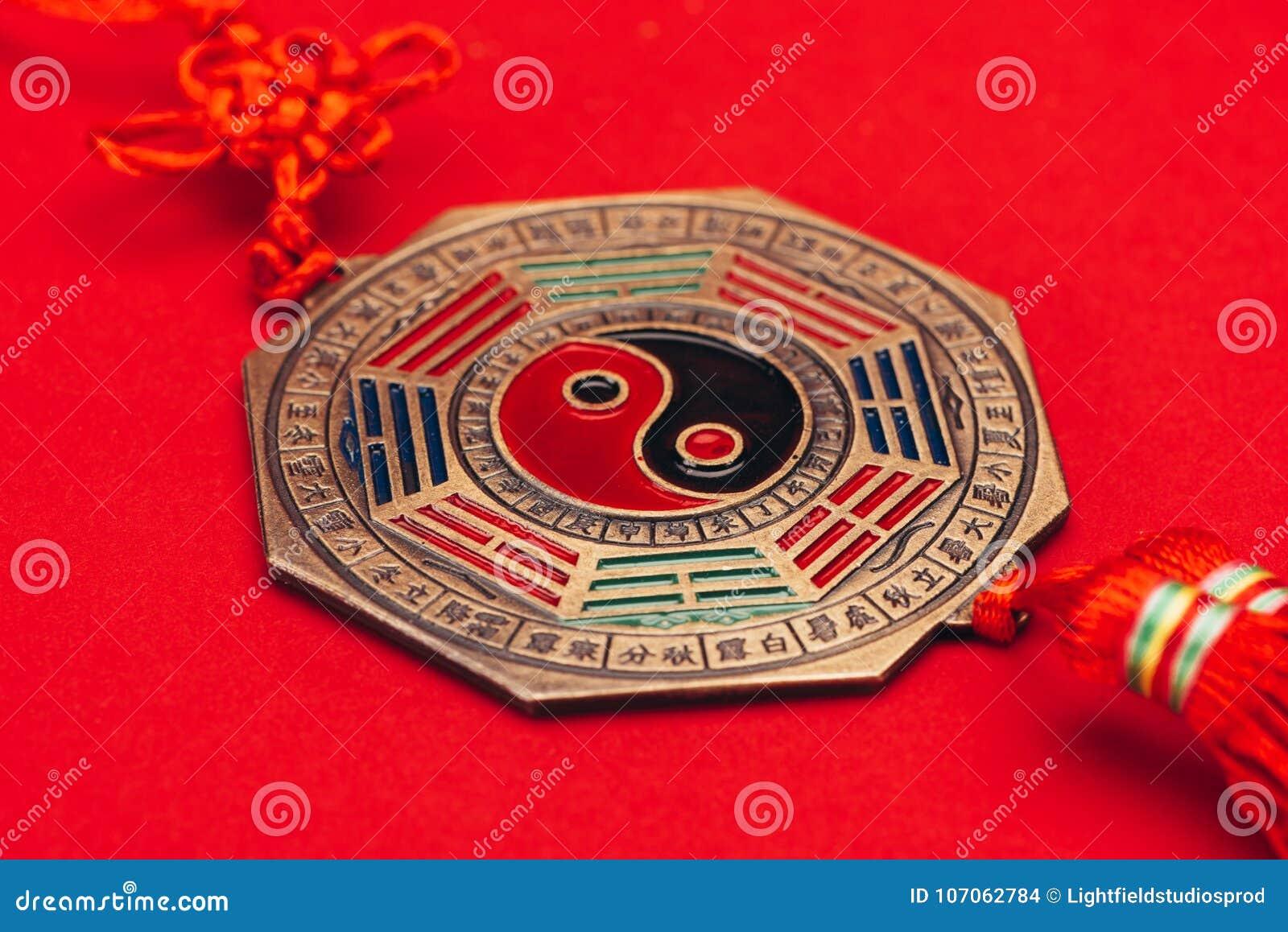 Yin för traditionell kines och yang amulett på röd yttersida