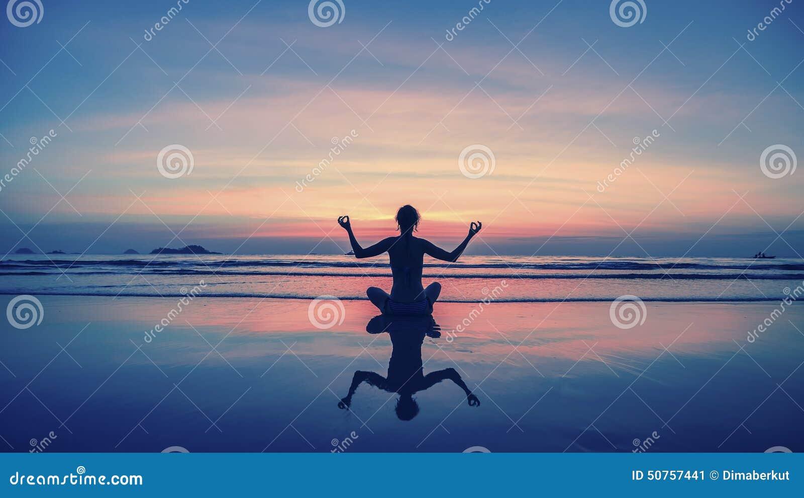 Yoga, aptitud, forma de vida sana Siluetee a la muchacha de la meditación en el fondo del mar y de la puesta del sol imponentes