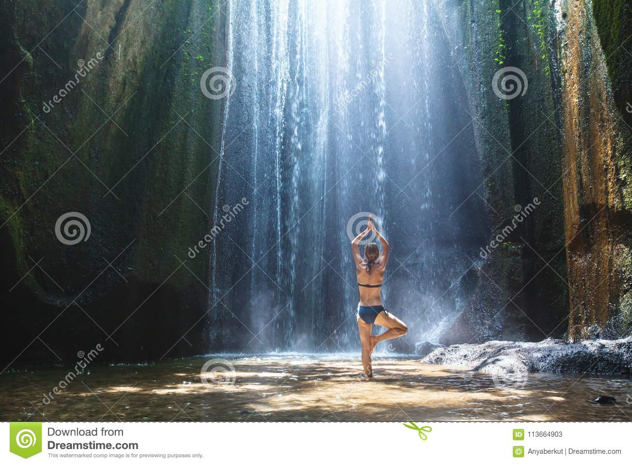 Yoga, beautiful woman practices in waterfall, body and mind harmony