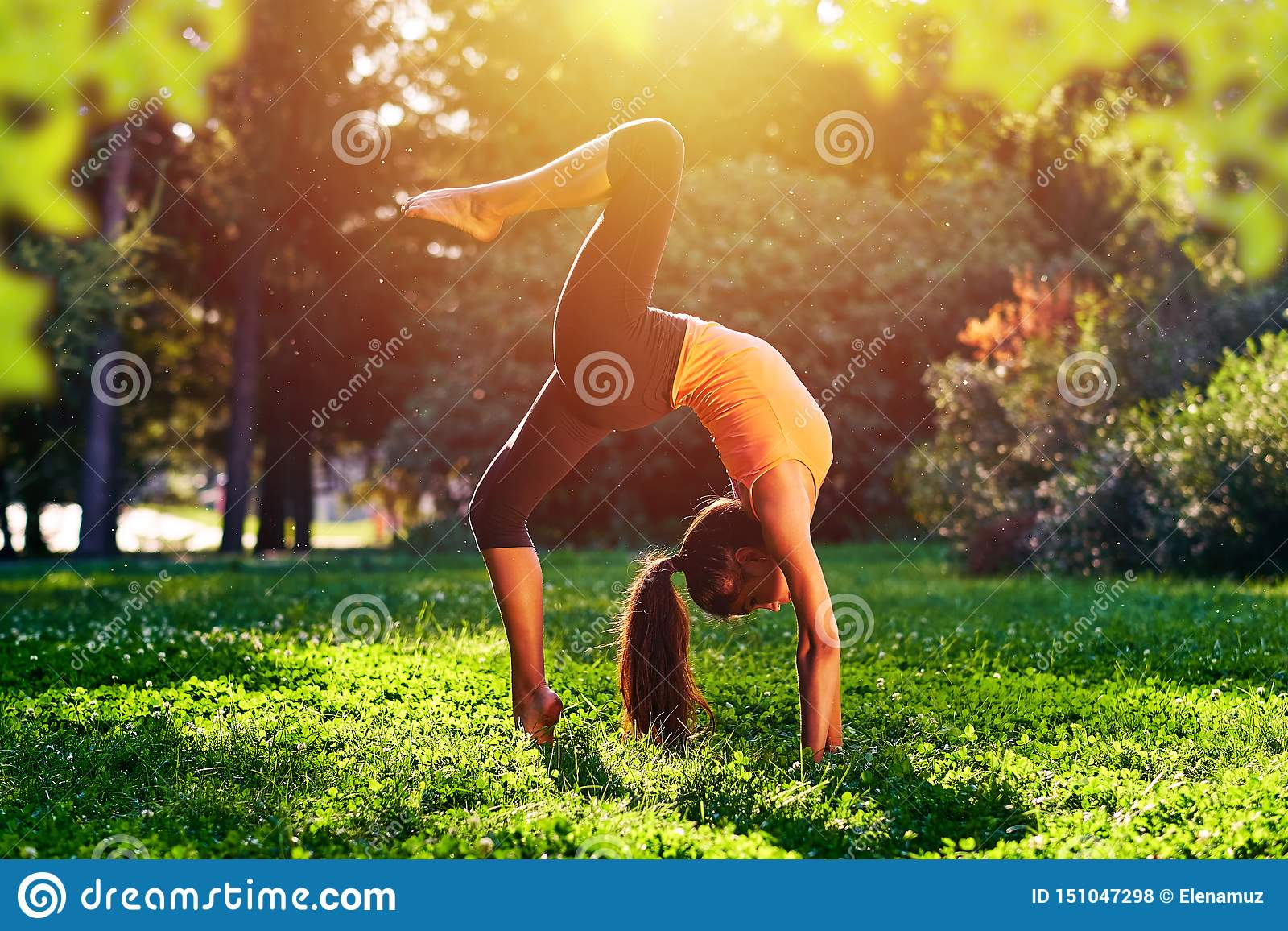 Yoga. Bridge exercise. Young woman practicing yoga or dancing or stretching in nature at park. Health lifestyle concept