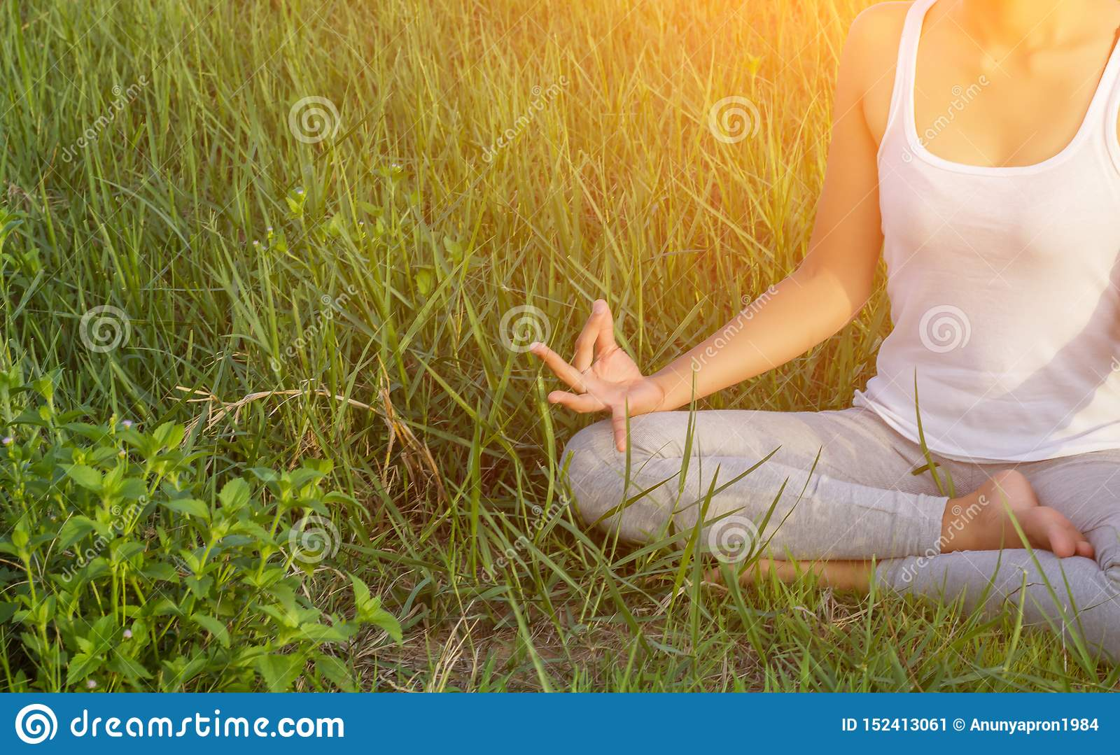Yoga in the city: beautiful young fit woman wearing sportswear meditating, breathing, sitting with crossed legs in Half Lotus