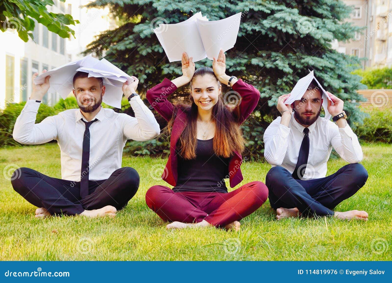Yoga de bureau Trois jeunes employés dans une pose de lotus s asseyent sur l herbe verte et méditent Récréation de personnel admi