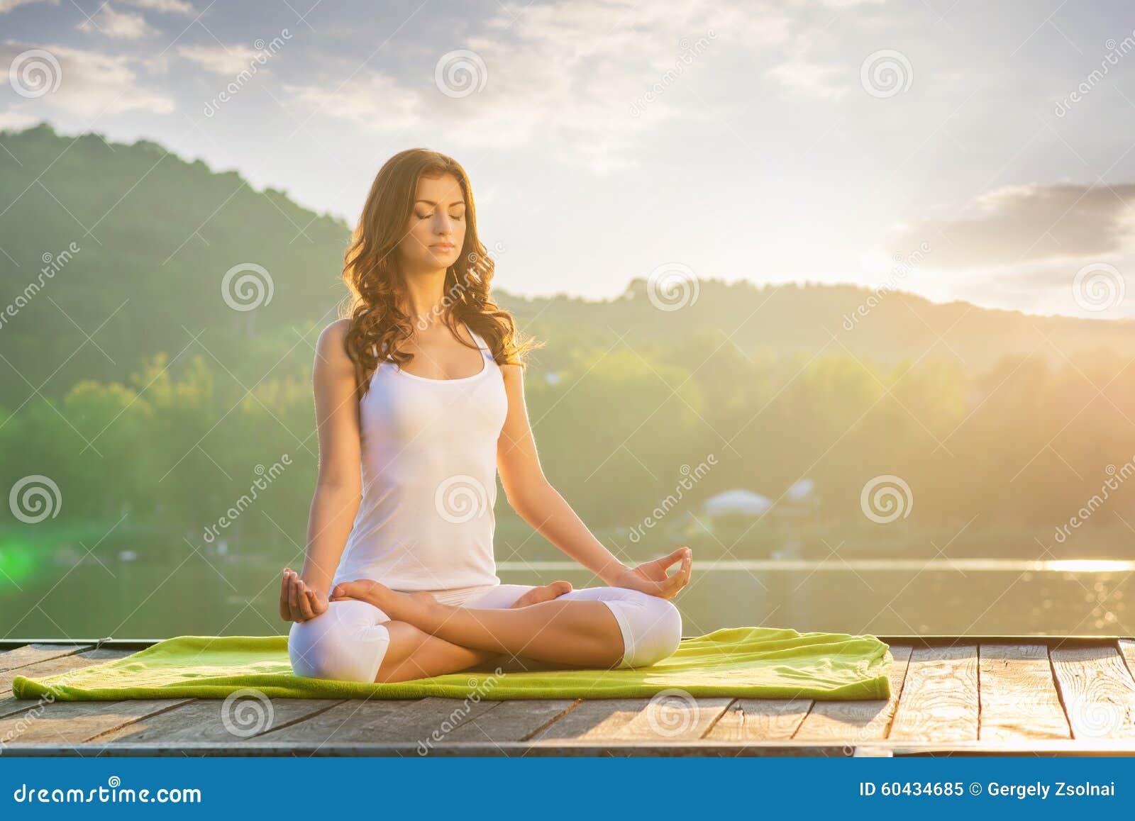 Yoga de femme - détendez en nature sur le lac