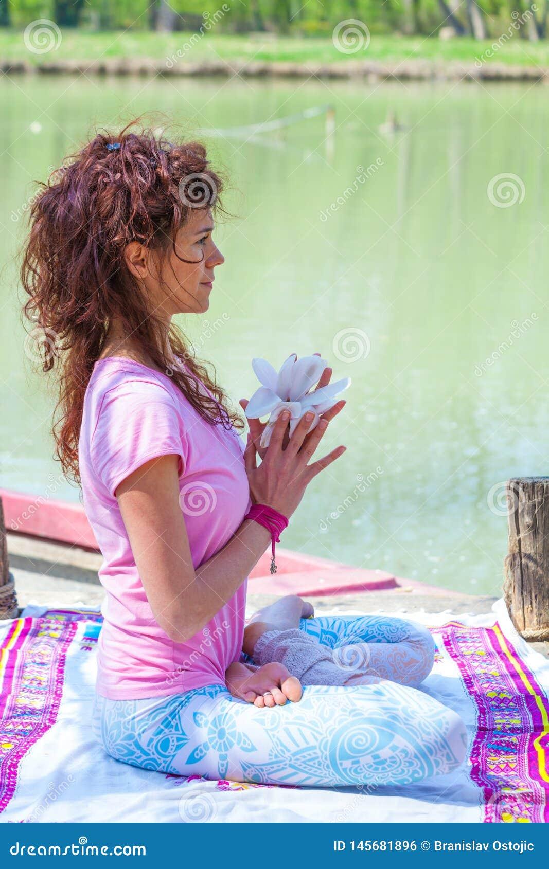 Yoga de la práctica de la mujer joven al aire libre por el concepto sano de la forma de vida de la flor de la magnolia del contro
