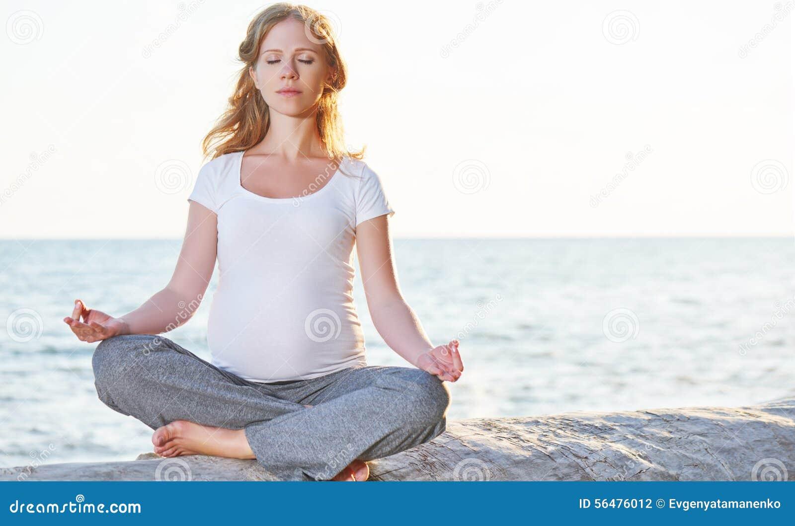 Yoga de pratique de femme enceinte en position de lotus sur la plage au soleil