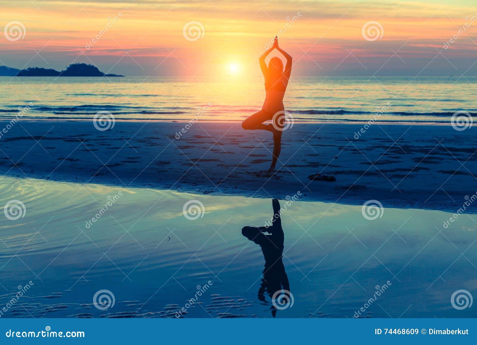 Yoga de pratique de jeune femme sur la plage au coucher du soleil avec la réflexion dans l eau