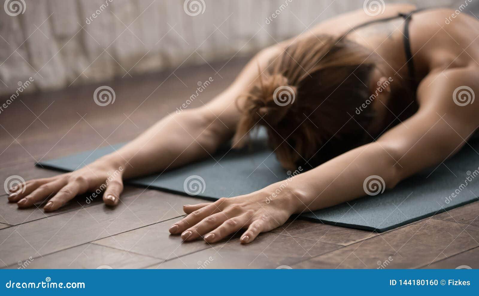 Yoga de pratique de femme attirante, détendant après avoir formé, visage menteur vers le bas