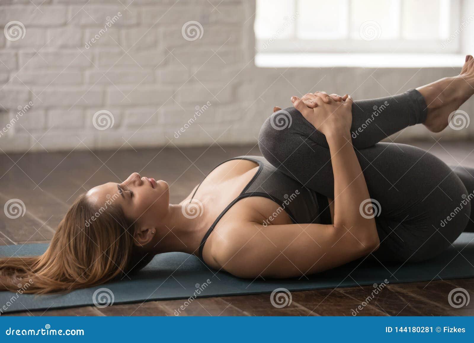 Yoga de pratique de femme, genoux à la pose de coffre, Apanasana, fin