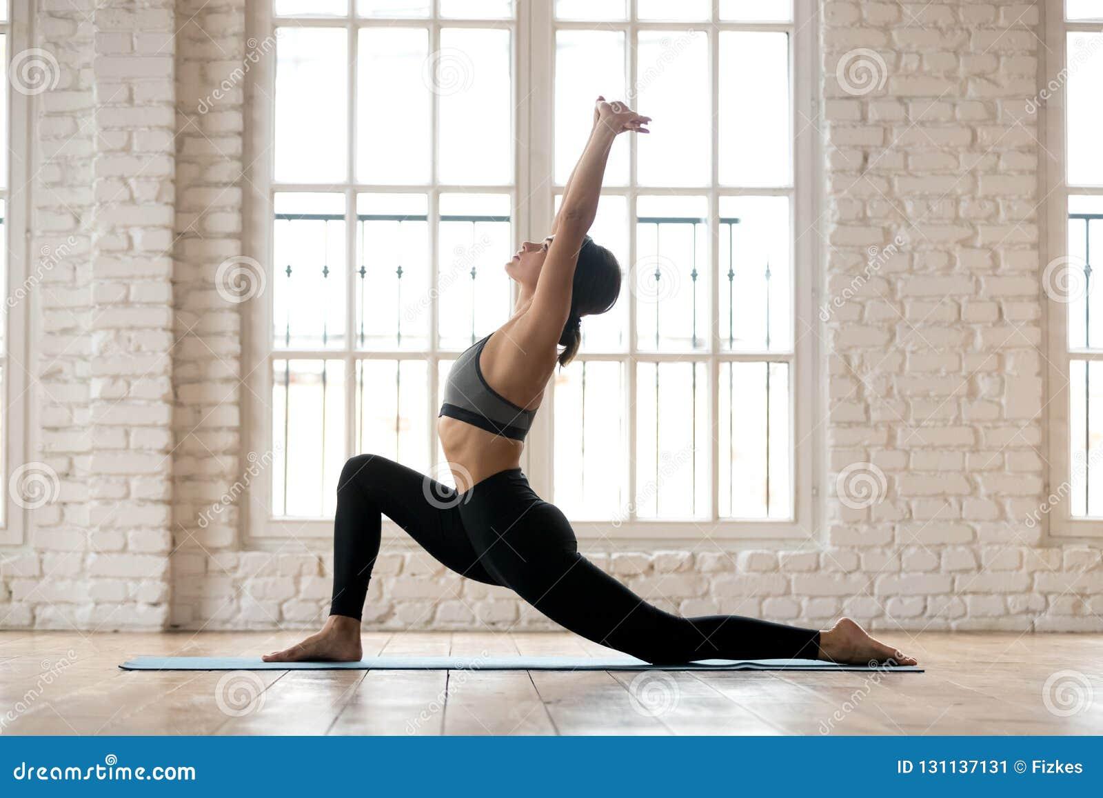 Yoga de pratique de jeune femme attirante de yogi, faisant le cavalier e de cheval