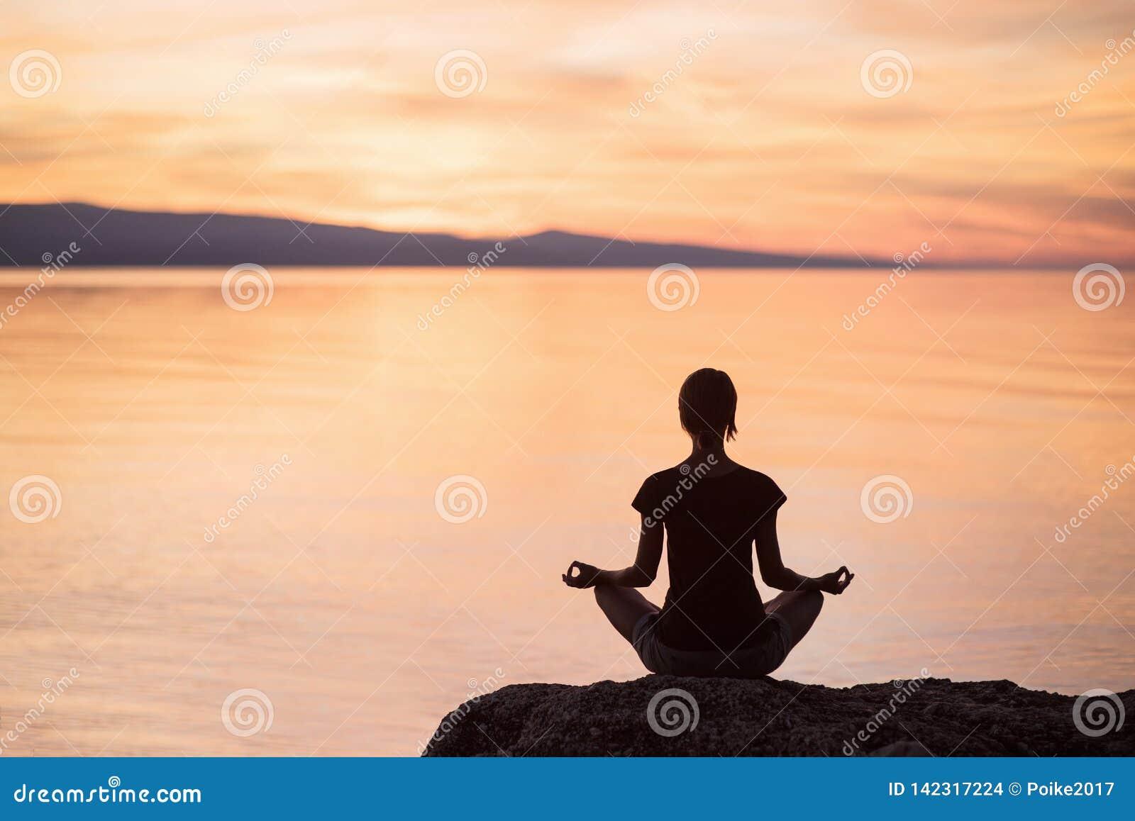 Yoga de pratique de jeune femme près de la mer au coucher du soleil Harmonie, méditation et concept de voyage Style de vie sain