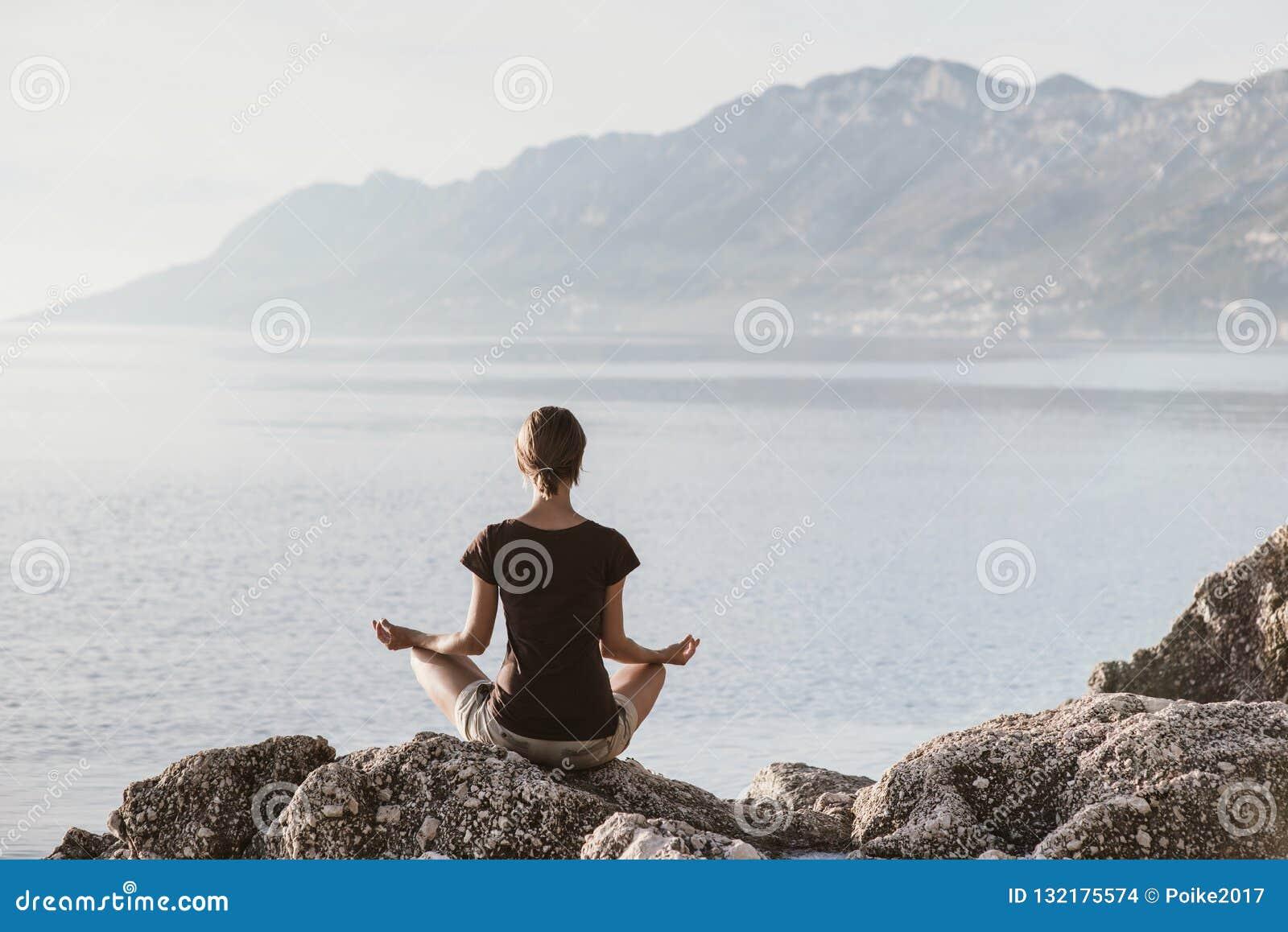 Yoga de pratique de jeune femme près de la mer Concept d harmonie et de méditation