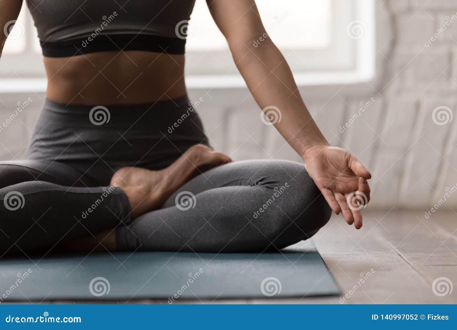 Yoga de pratique de jeune femme, se reposant dans la pose de Padmasana, exercice de Lotus