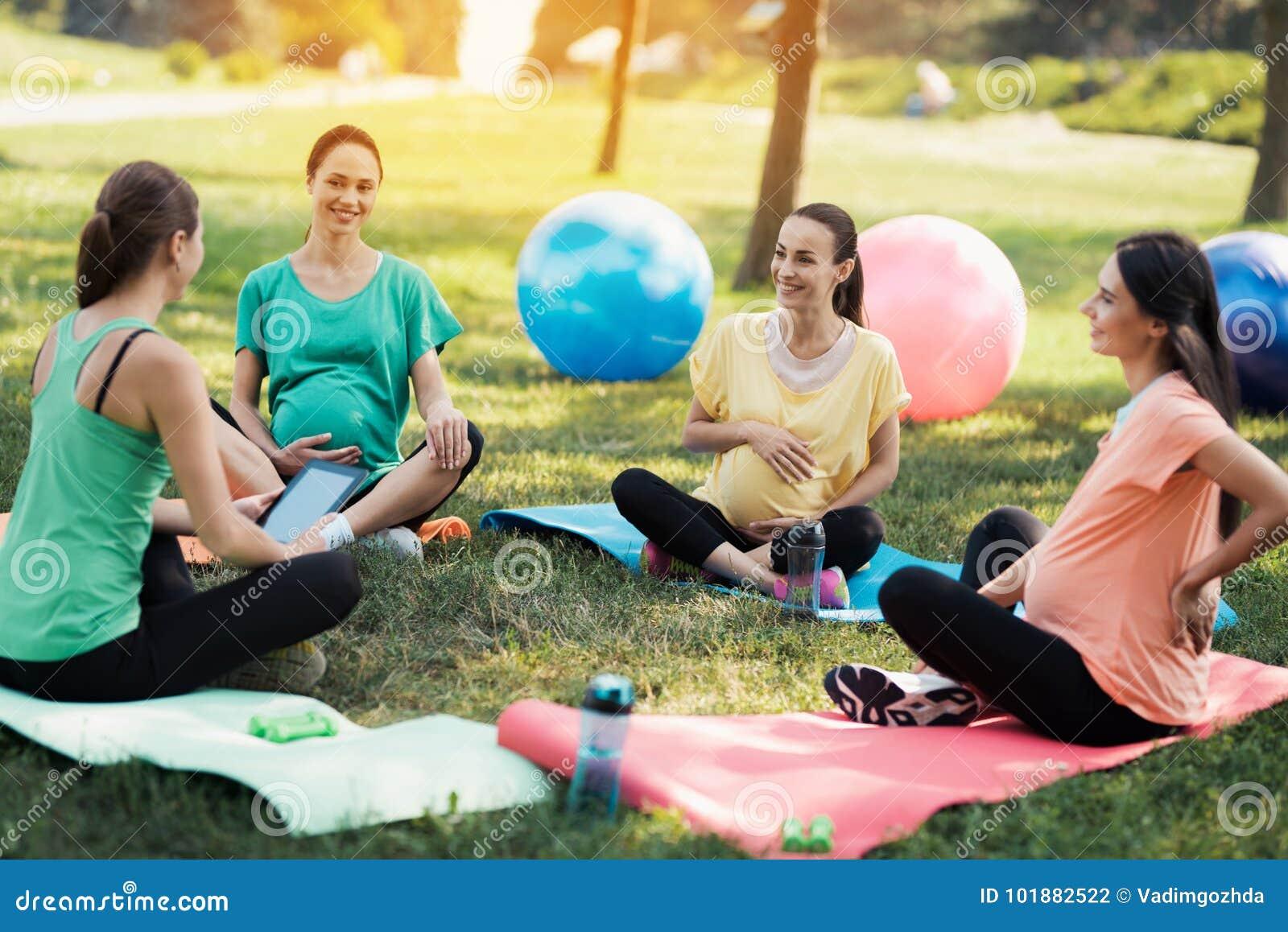 Yoga del embarazo Un instructor femenino se sienta delante de tres mujeres embarazadas que vinieron a la yoga