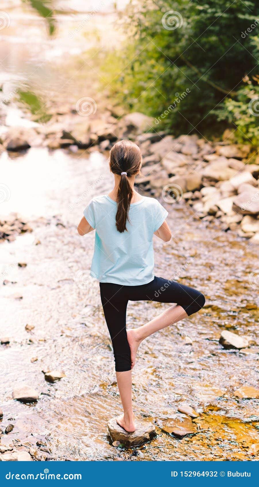 Yoga des jungen Mädchens, das bei dem Sonnenaufgang sitzt auf Steinen auf dem Ufer eines Gebirgsstromes meditiert Jugendmodell, d