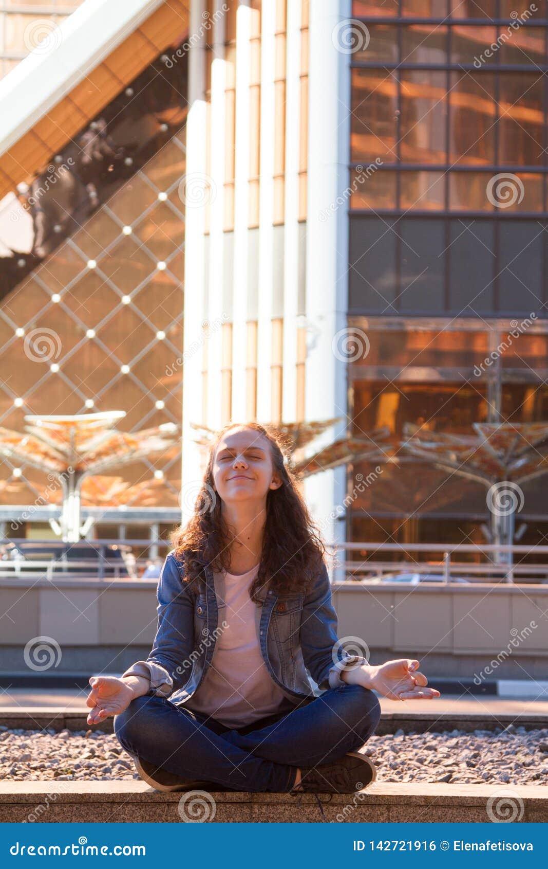 Yoga des jungen Mädchens und meditiert im Lotussitz in einer Großstadt