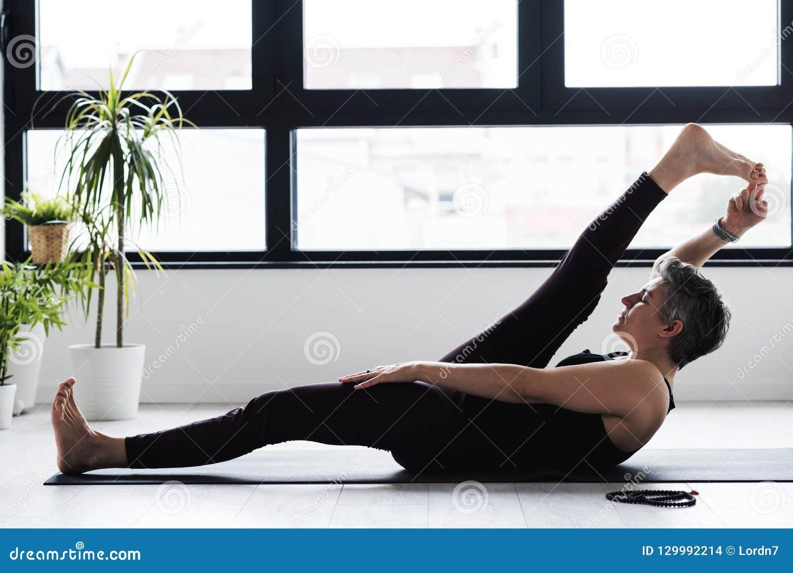 Yoga di pratica della donna caucasica matura sul pavimento del salone