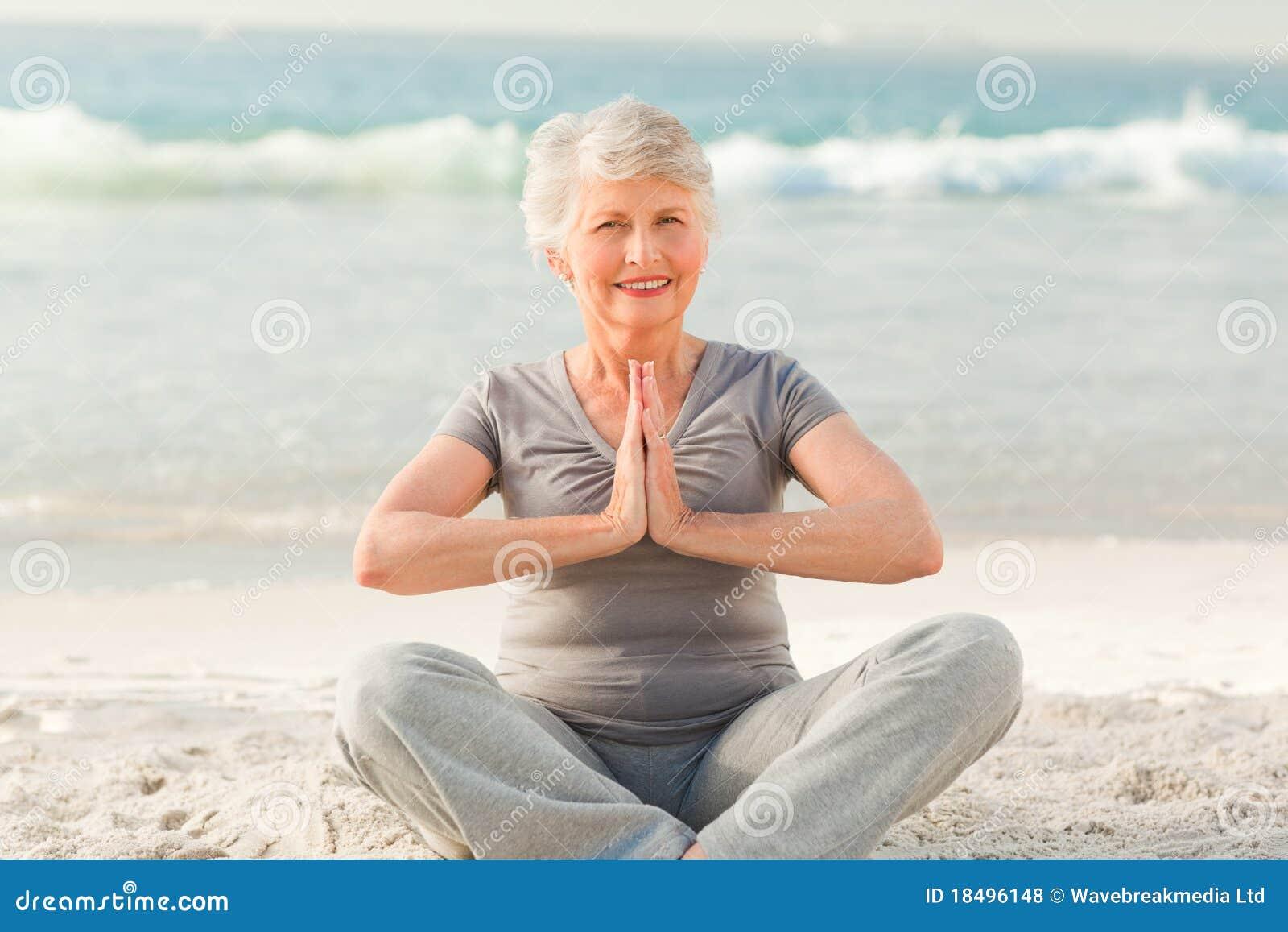 Yoga di pratica della donna maggiore sulla spiaggia