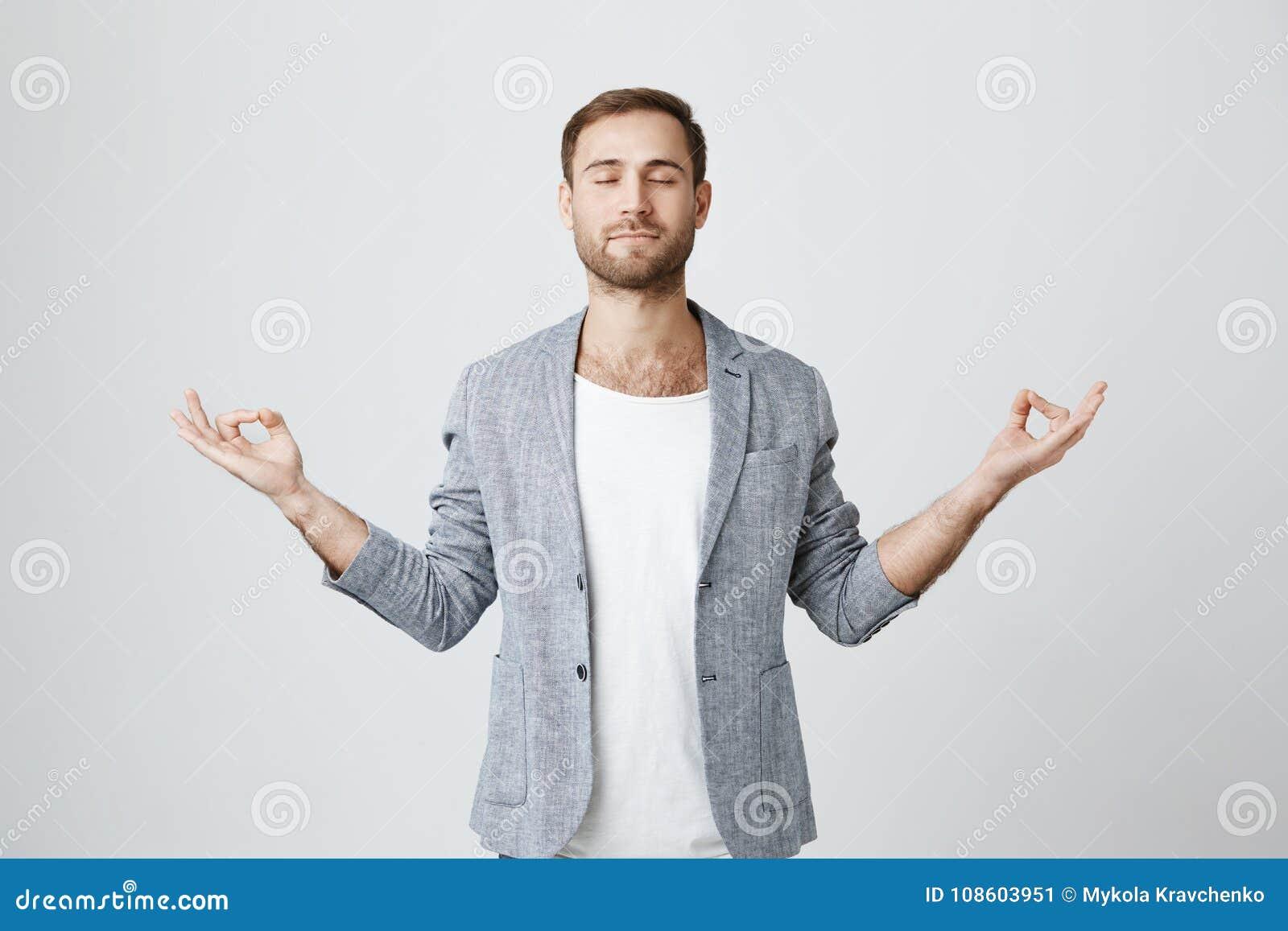 Yoga en meditatie De knappe mens met baard kleedde zich in jasje die ogen gesloten houden terwijl het mediteren, ontspannen voele