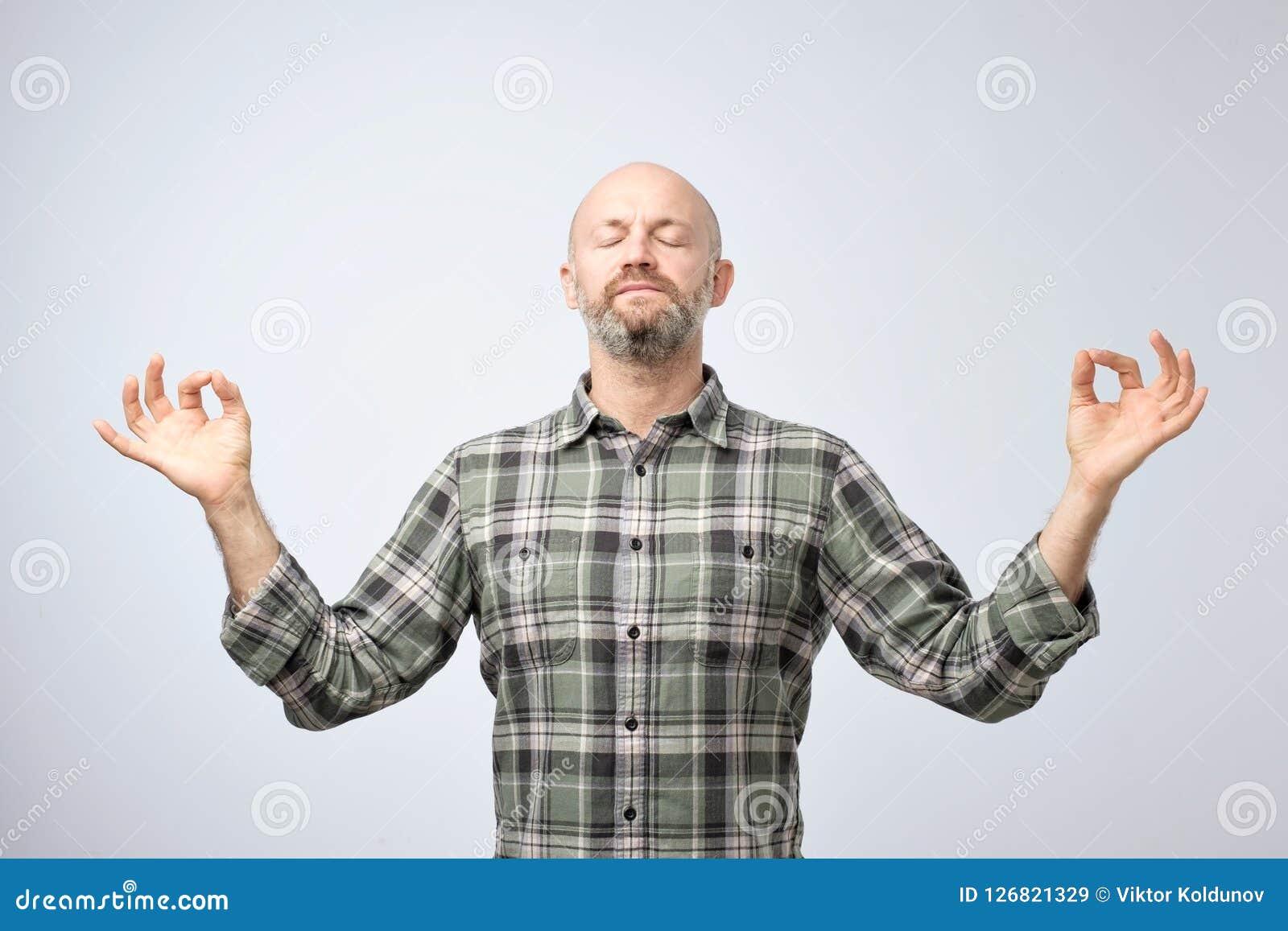 Yoga en meditatieconcept De knappe kale mens met varkenshaar die ogen houden sloot terwijl het mediteren