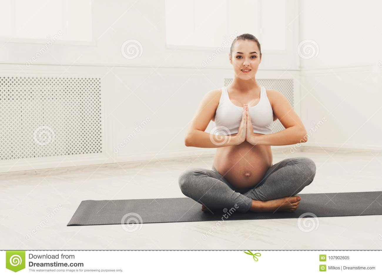 Yoga heureux de formation de femme enceinte dans la pose de lotus